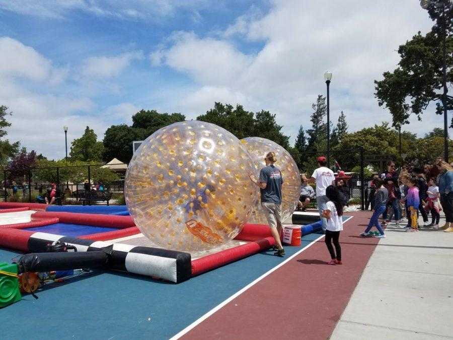 People+line+up+for+an+activity+called+Zorbing%2C+where+the+player+rolls+around+in+a+clear+plastic+ball.
