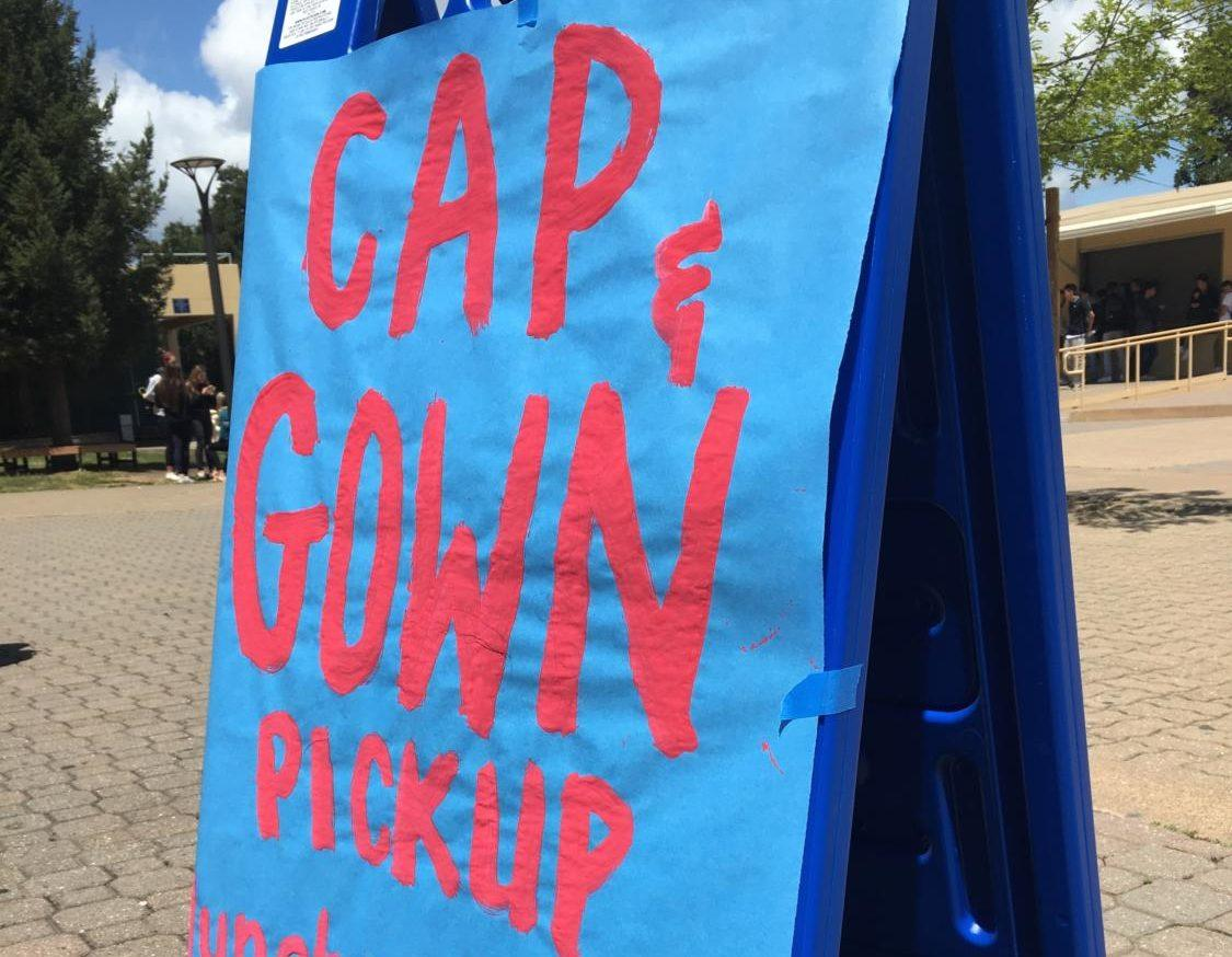 A sign displayed in the quad shows seniors where to go to pick up their caps and gowns.