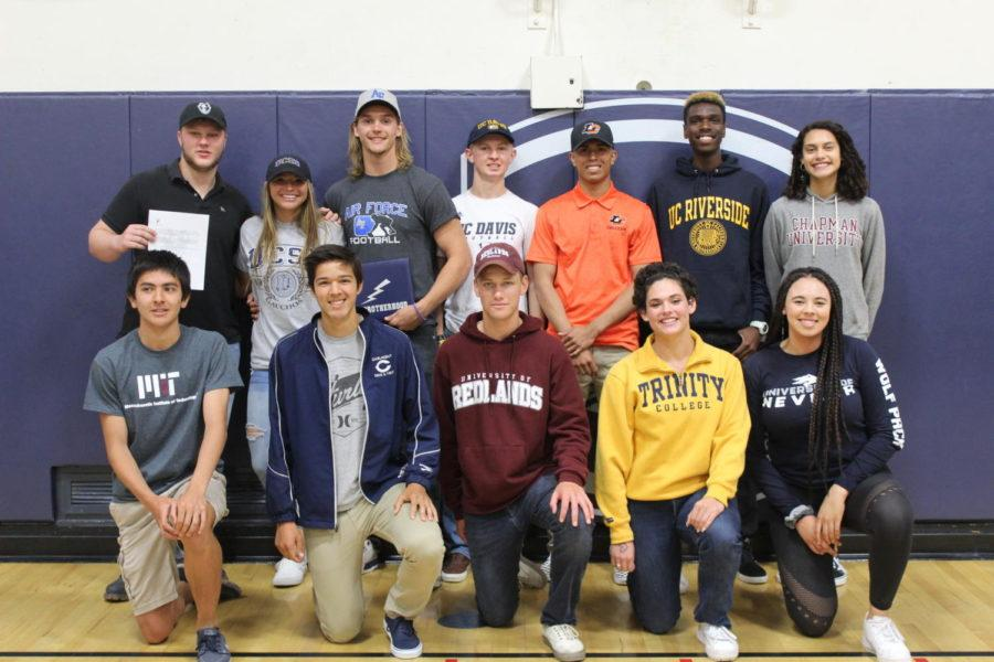 Seniors who signed to college sports teams take a picture during the signing ceremony.