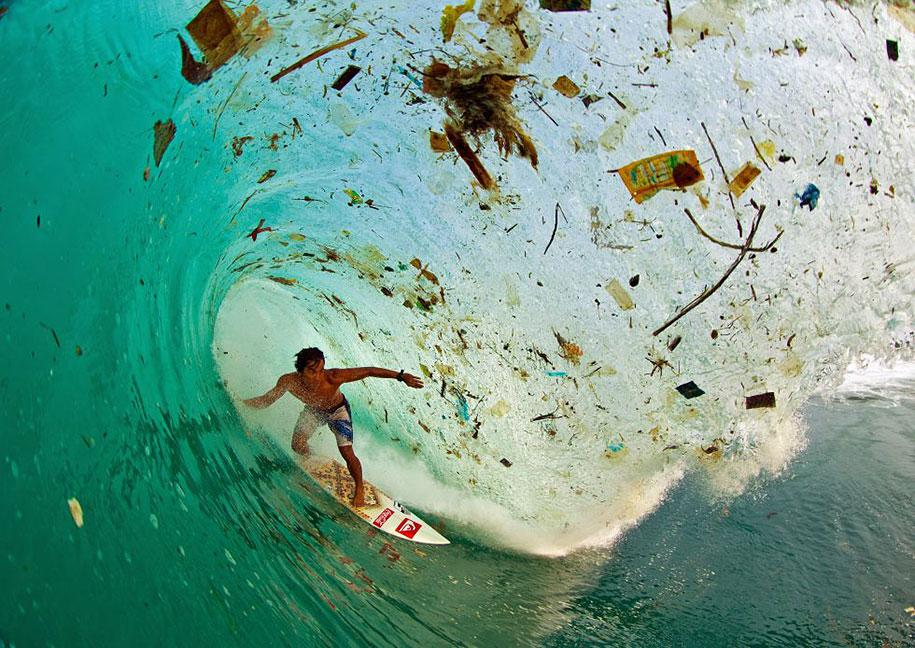 Surf champion, Dede Suryana, rides a wave filled with trash in Indonesia.