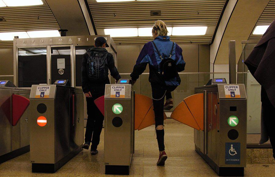 BART riders place their tickets through the ticket machine as they walk through the barriers.