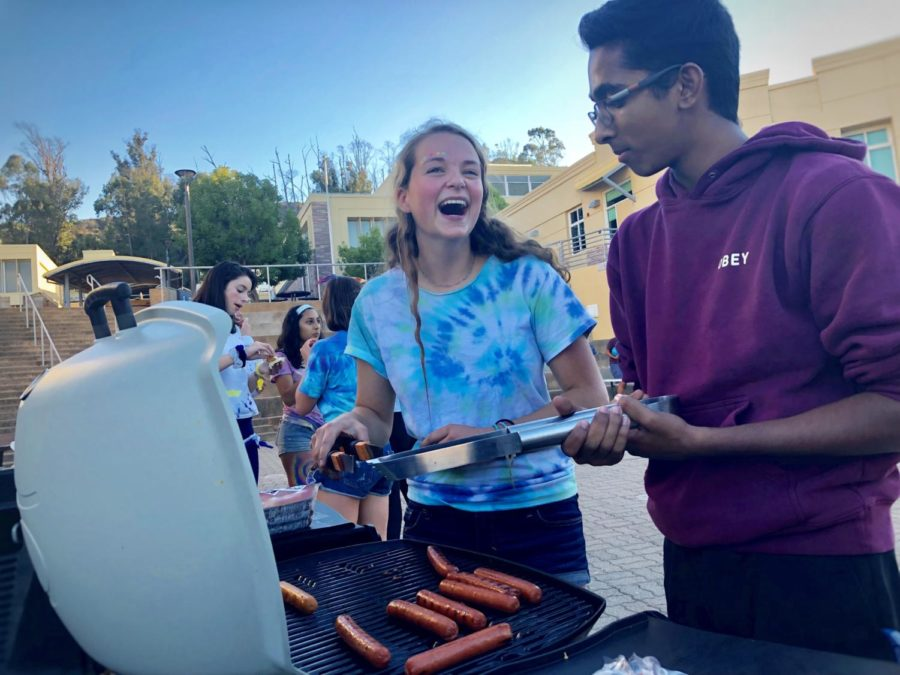 Juniors Ayan Dixit and Greta Foehr grill hotdogs for students during the ASB Tie-dye Tailgate.