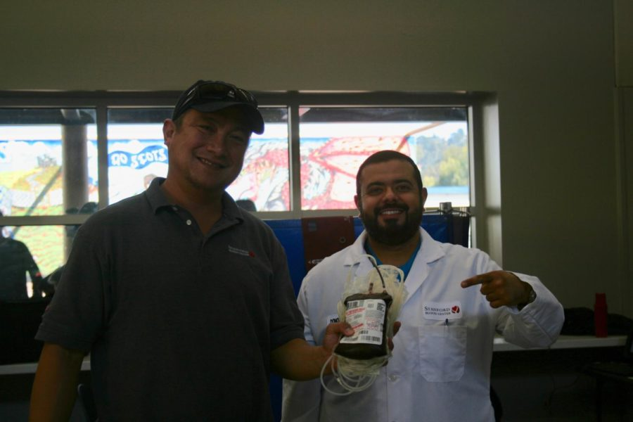 Two blood technicians from Stanford hold up a pint of blood that is ready to be donated.