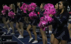 Carlmont's cheer team raises their pink pom-poms during varsity football's home game against Capuchino in support of breast cancer survivors.