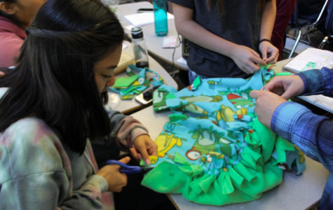 Kristine Chan, a senior, helps her friends make a blanket.