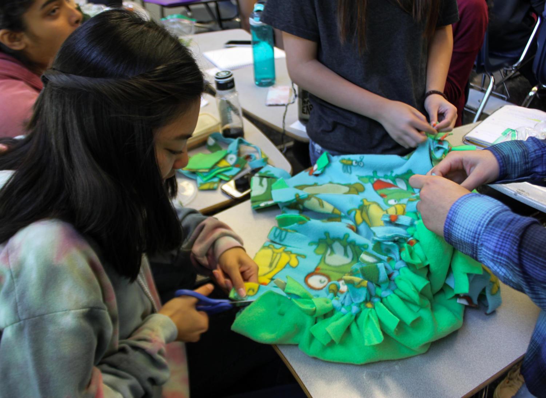 Kristine Chan, a senior, helps her friends make a blanket.