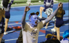 Senior Timothy Krassiev leads the Screamin' Scots section at the Homecoming football game, Oct. 26.