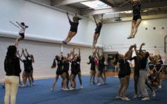 Flyers Sophia Morgan, Tara Bakhtegan, Taryn Schloss, and Sadie Lyman fly through the air in the middle of a basket toss stunt.
