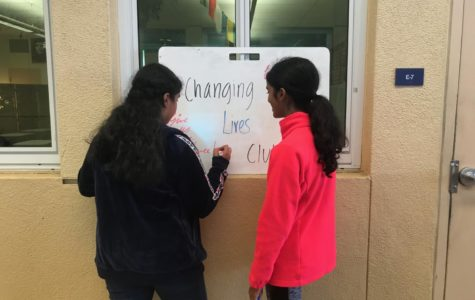Sarga Nair and Varsha Raj create the sign for the Changing Lives Club.