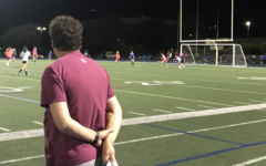 Varsity girls soccer head coach watches players scrimmage during tryouts.