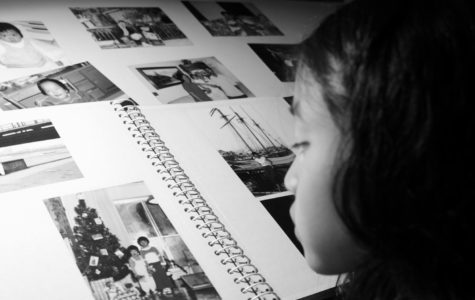 An adopted child looks at photos of her unknown biological bloodline.