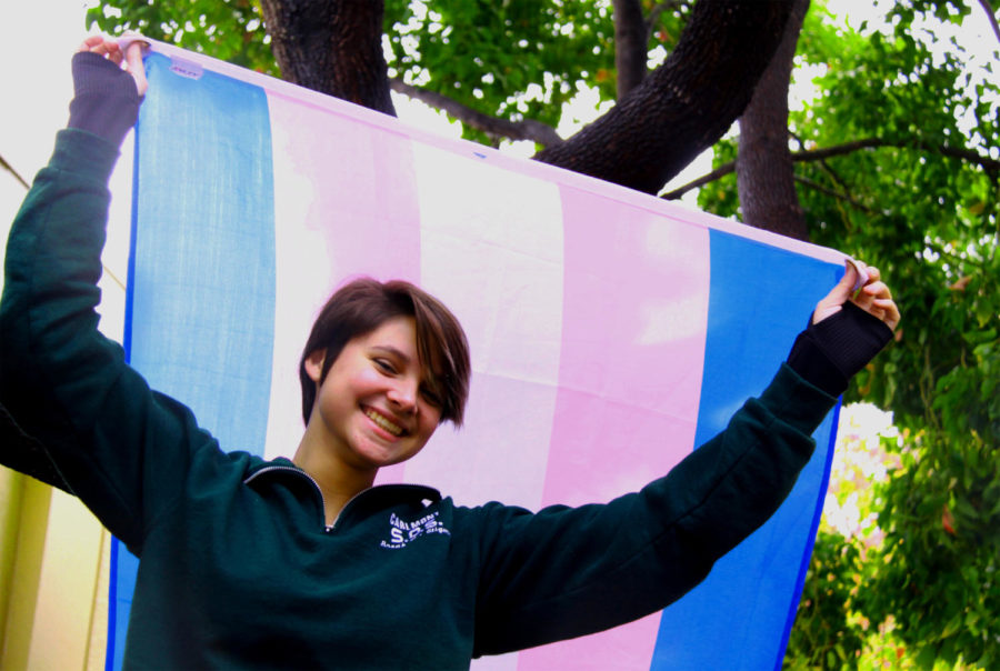 Transgender student Alex Nyholm-Goncalves, who identifies as gender non-conforming, holds up the trans flag with pride.
