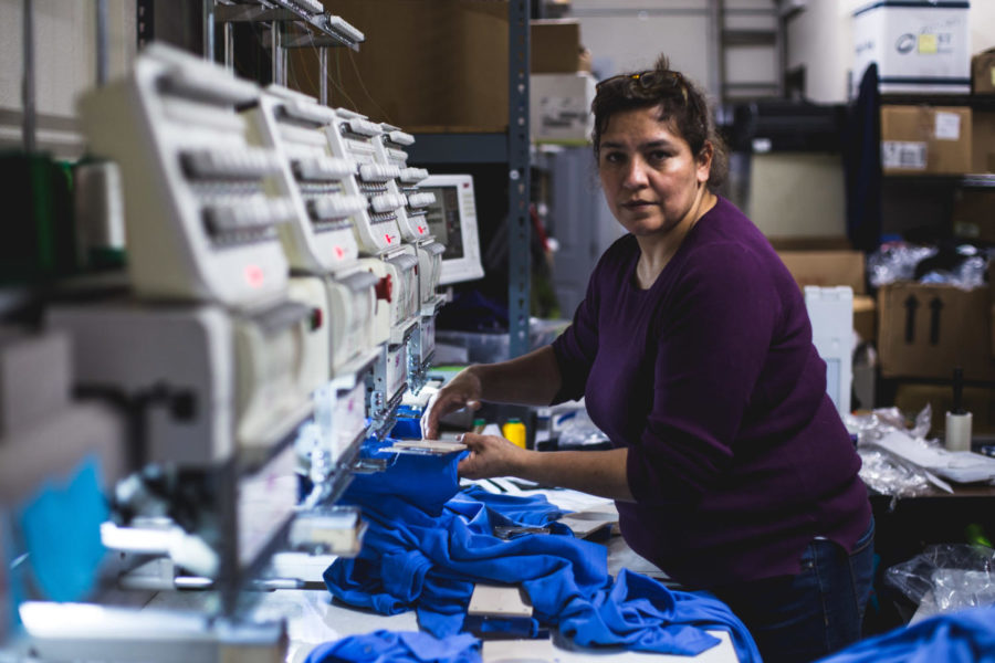 Immigrant Marisol Villegas works newly designed clothing on embroidery machines at her small business.