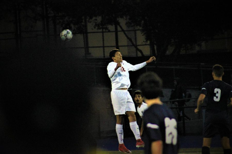 A+member+of+the+JV+boys+soccer+team+leaps+for+a+header+in+the+middle+of+a+game.