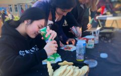 Soni Kanaya and Chloe Palarca-Wong, both juniors, participate in one of the Holiday Village activities by decorating cookies in the quad.