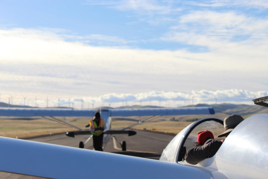 Instructor Buzz Graves and a student sit in a club glider, awaiting towline hookup and preparing for an aerotow takeoff.
