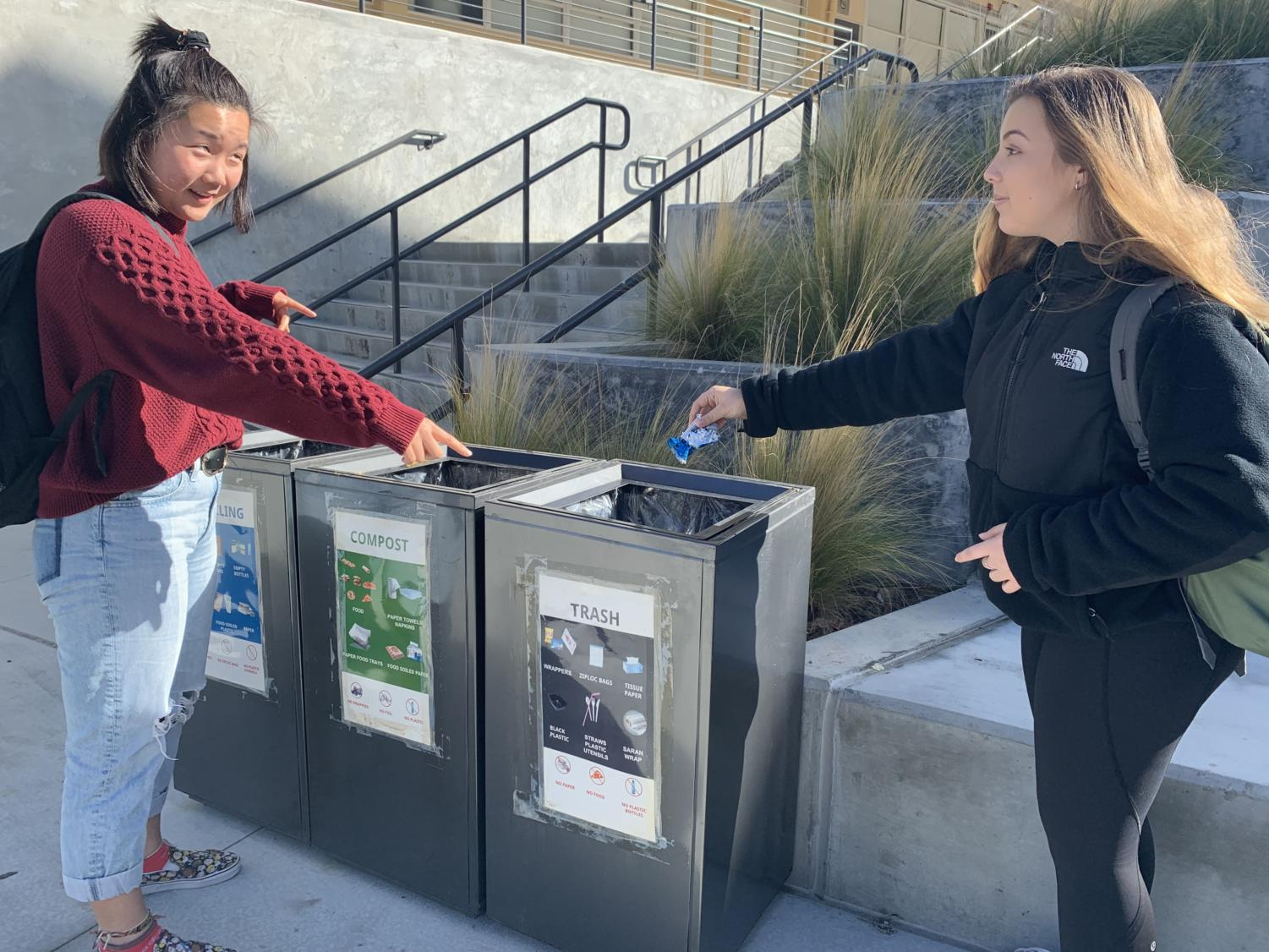 Eva Robertson, sophomore directs Liz Gurevich, sophomore, to the right bin to dispose of her trash.