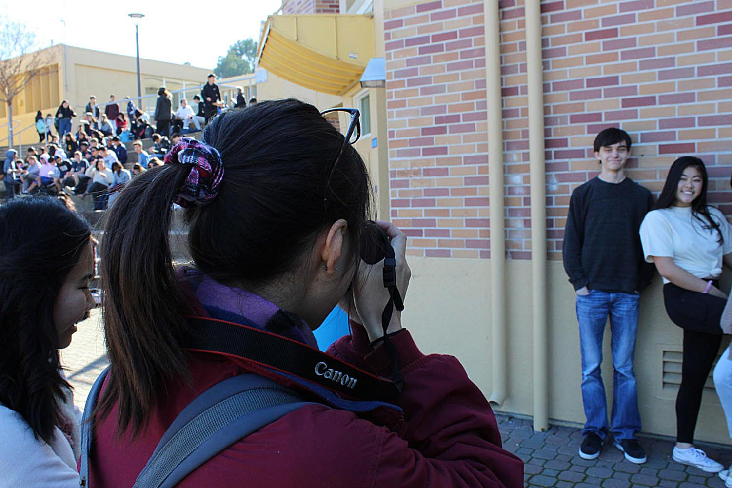 Lauren Chong takes a club photo for the yearbook in the quad.