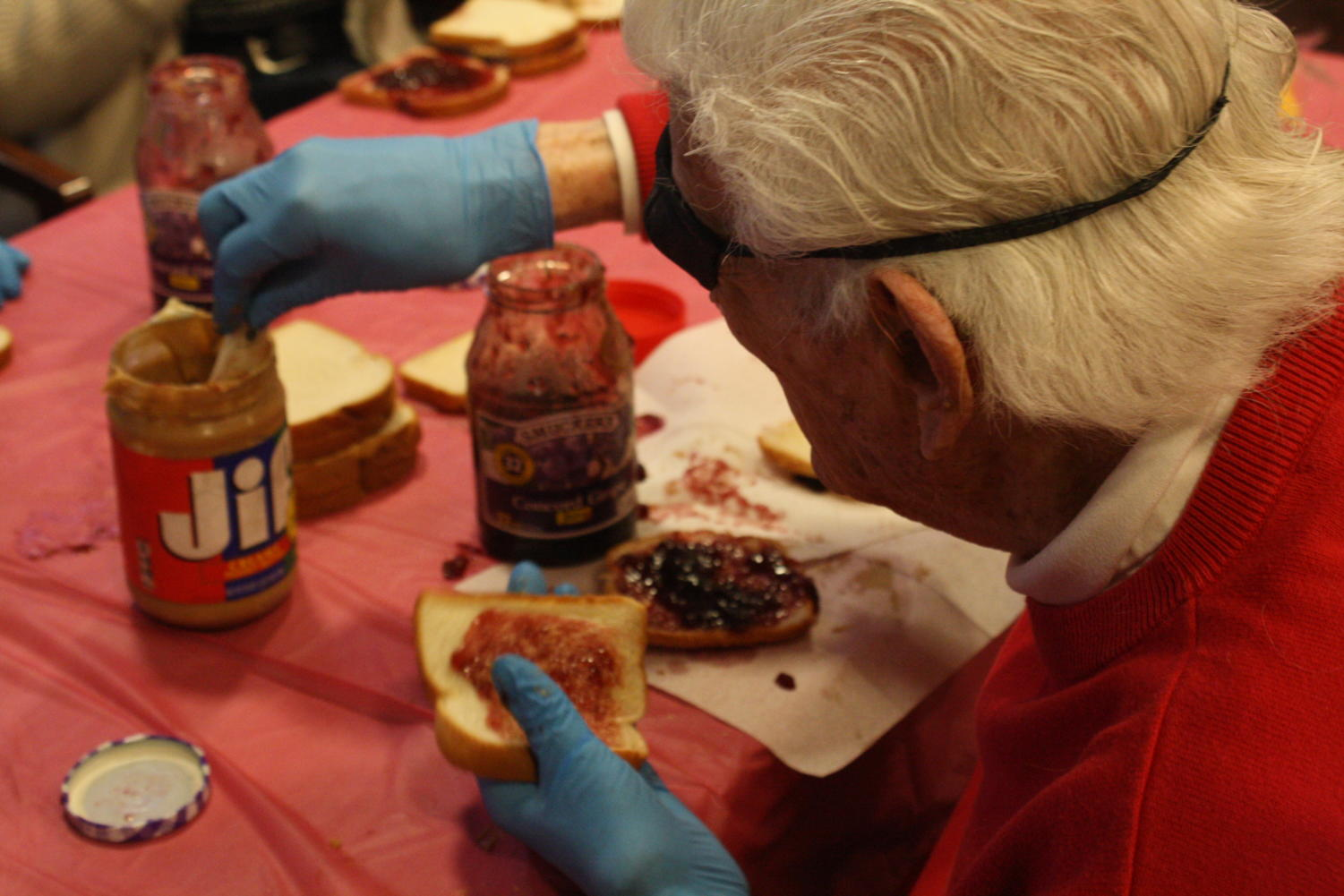 The senior citizens at the San Carlos Elms make peanut butter and jelly sandwiches for the homeless.