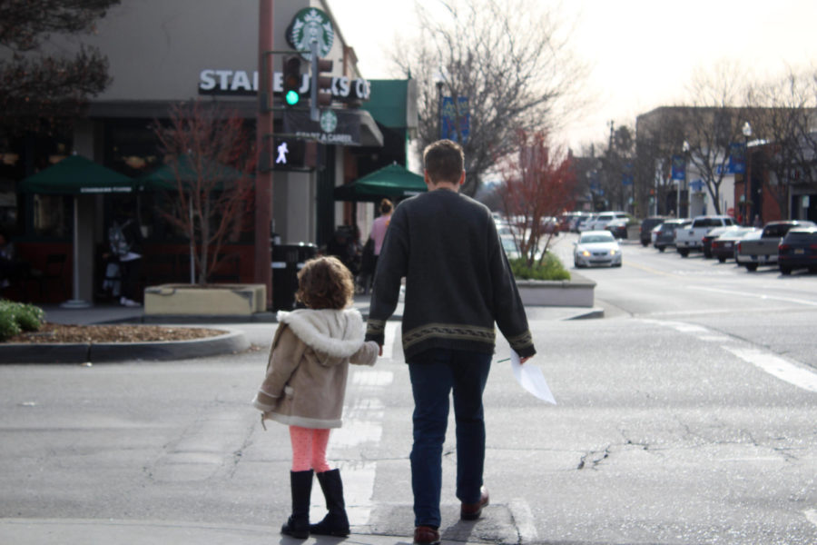 A+father+and+daughter+join+hands+while+crossing+the+street+to+their+next+destination.+