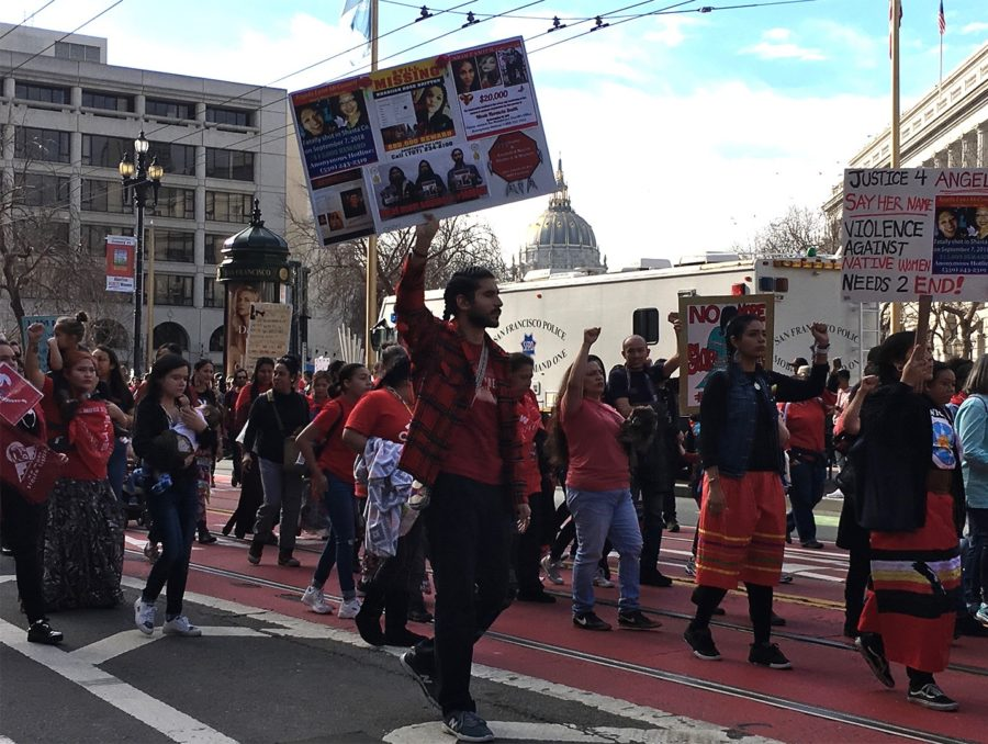 Participants of the march walk down Market Street with their posters.