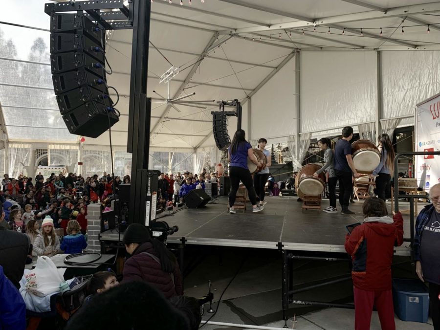 Volunteers help bring out the taiko drums while the crowd socializes.
