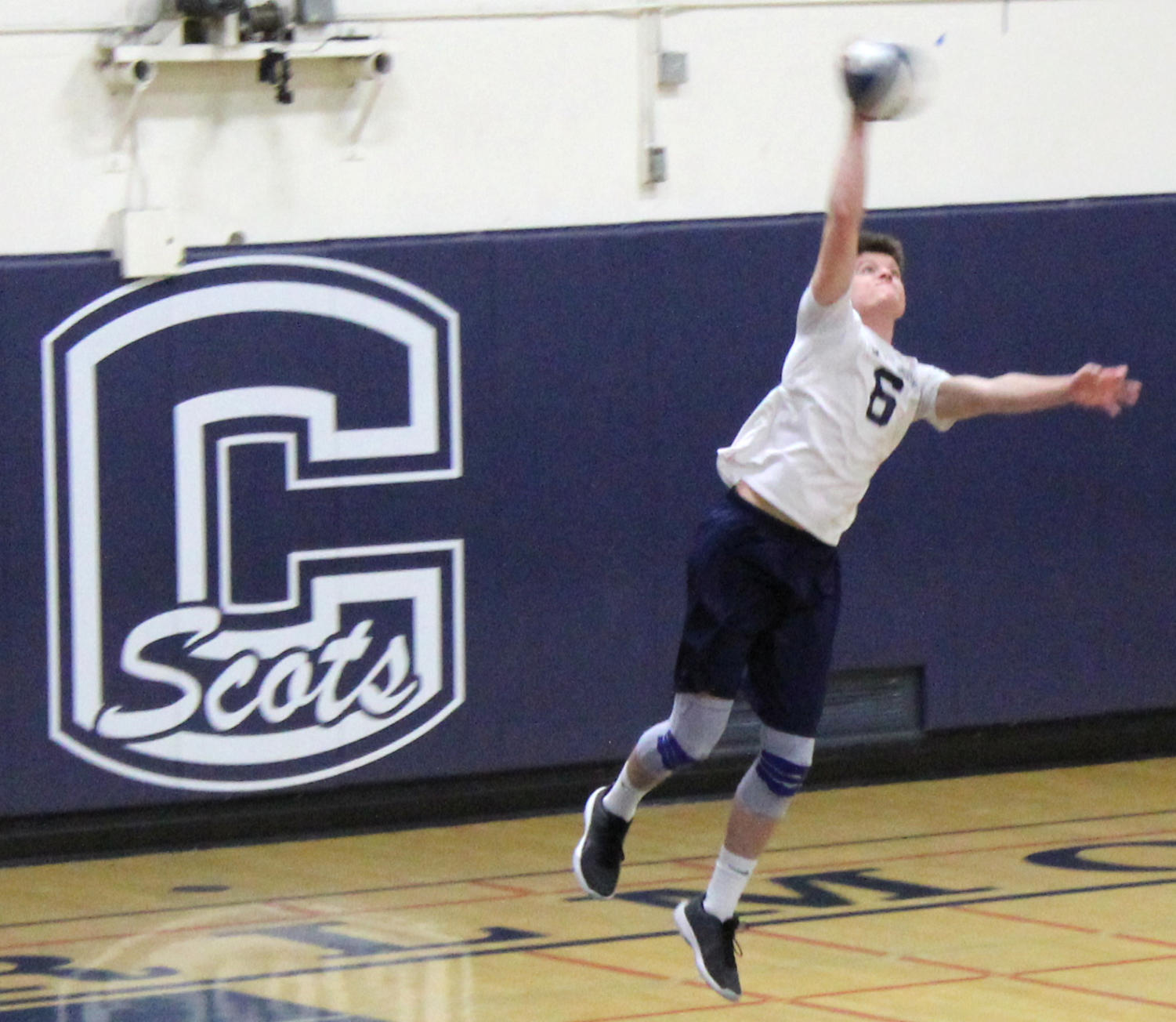 Ethan Mayoss, a junior, serves the ball during the first match
