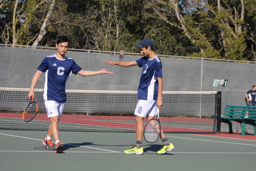 Jerry Lui, a senior, high-fives Iman Shafaie, a freshman, after a match.