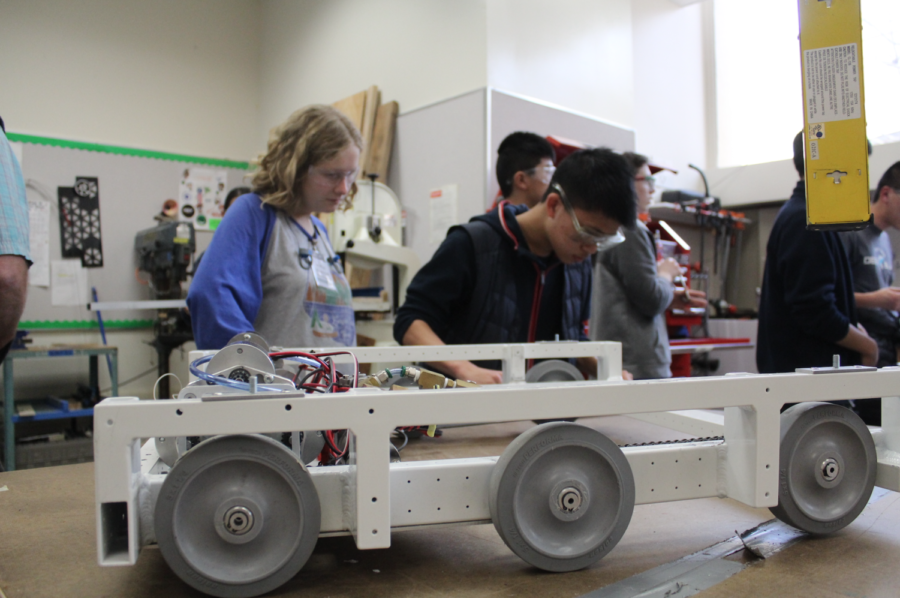 The team members in the Robotics Club divide up the responsibilities of preparing the practice robot in the workshop on Friday.