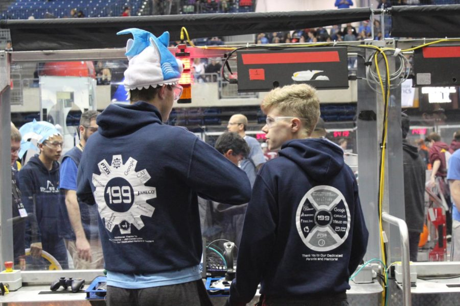 Two+Robotics+team+members+discuss+strategies+before+participating+in+their+competition.+