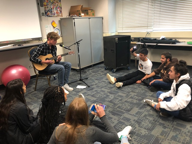 Students+gather+around+Keegan+Dyer+while+he+performs.