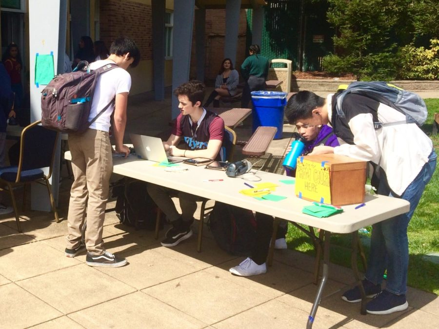 A student buys tickets for prom at lunch near the quad.
