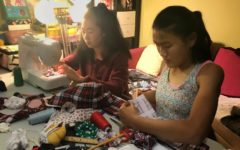Carolyn Wang and Emma Wang work hard to make scrunchies.