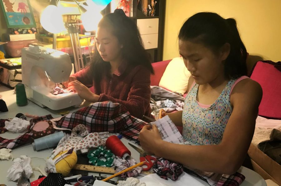 Carolyn Wang and Emma Wang work hard to make scrunchies.