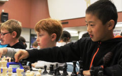 A boy reaches to hit the timer, signaling the end of his move against his opponent.