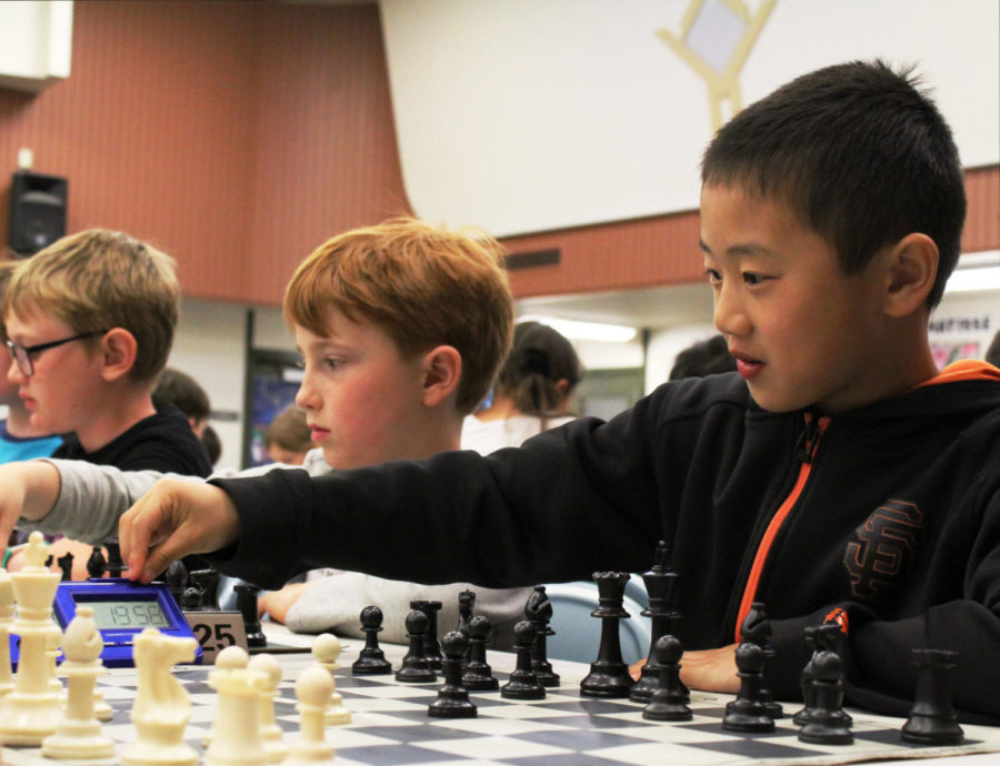 A+boy+reaches+to+hit+the+timer%2C+signaling+the+end+of+his+move+against+his+opponent.+