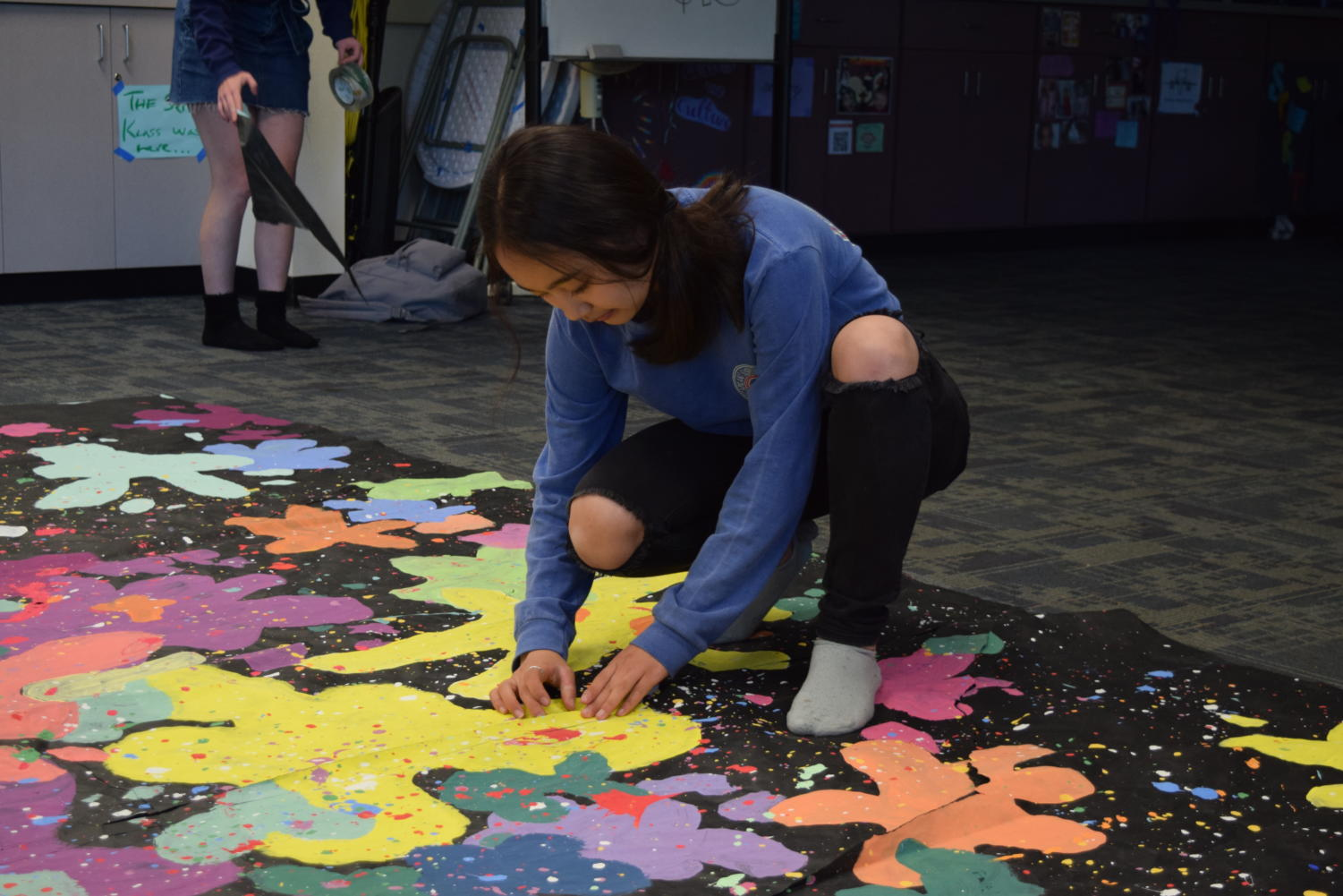 Rachel Gu, a senior and supervisor of activities in publicity, tapes up a damaged banner.