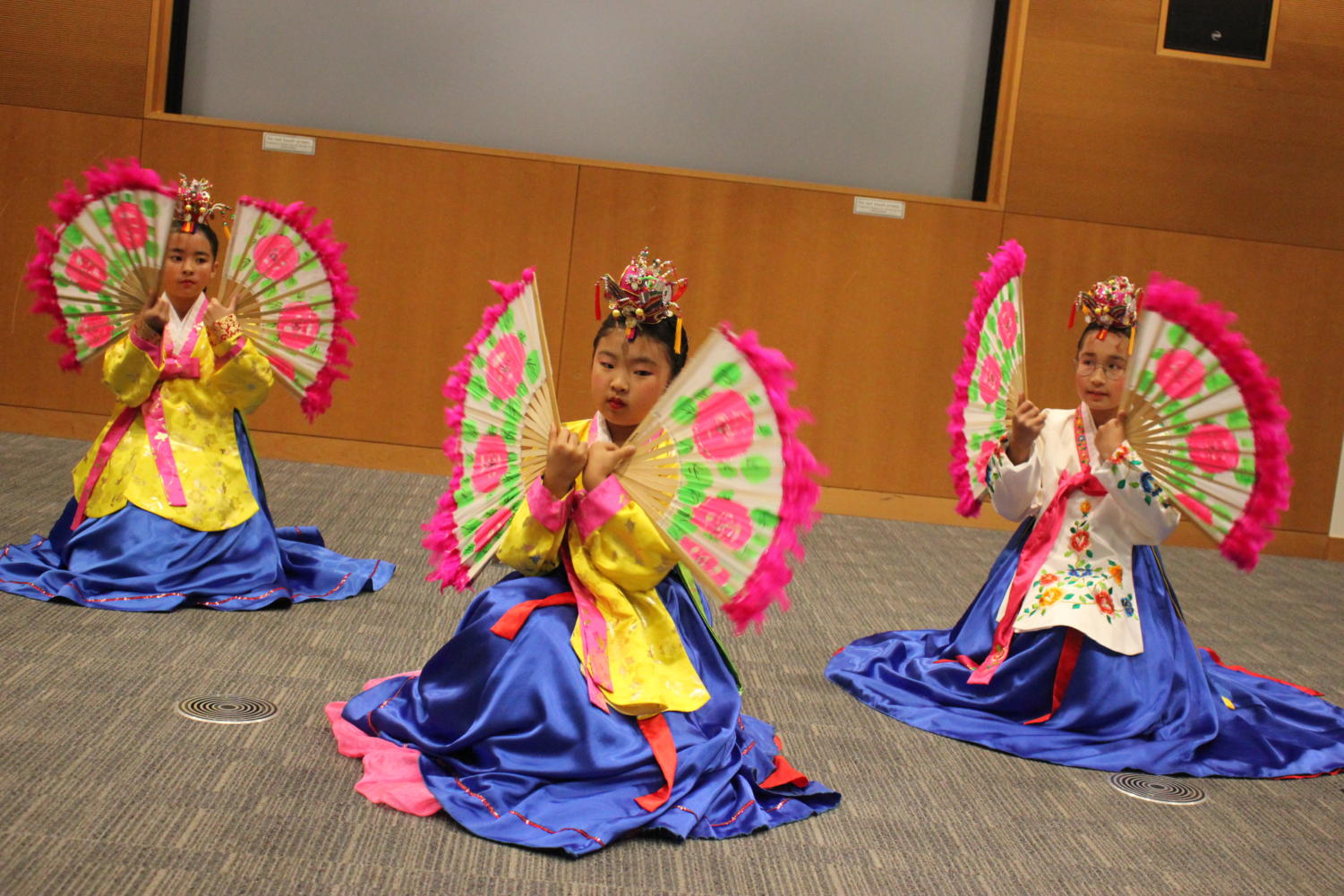 Korean dancers wave brightly colored fans decorated with flowers.