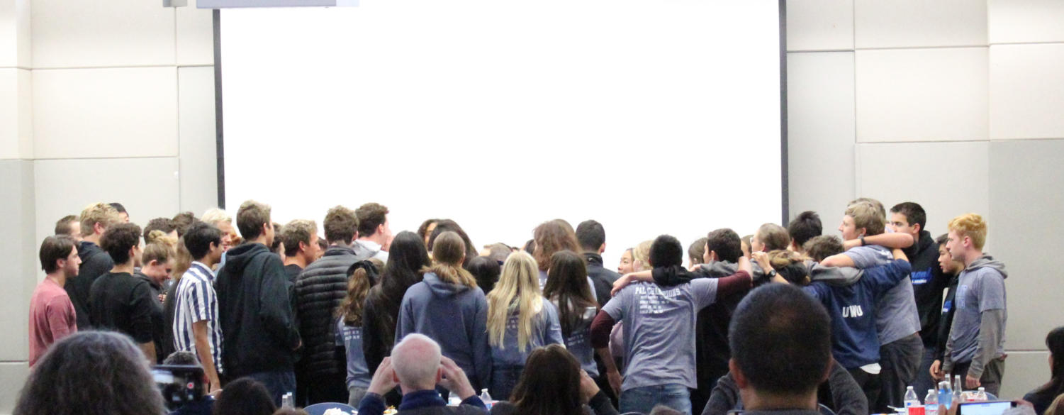 All of the Carlmont swimmers gather to chant their final cheer of the season.