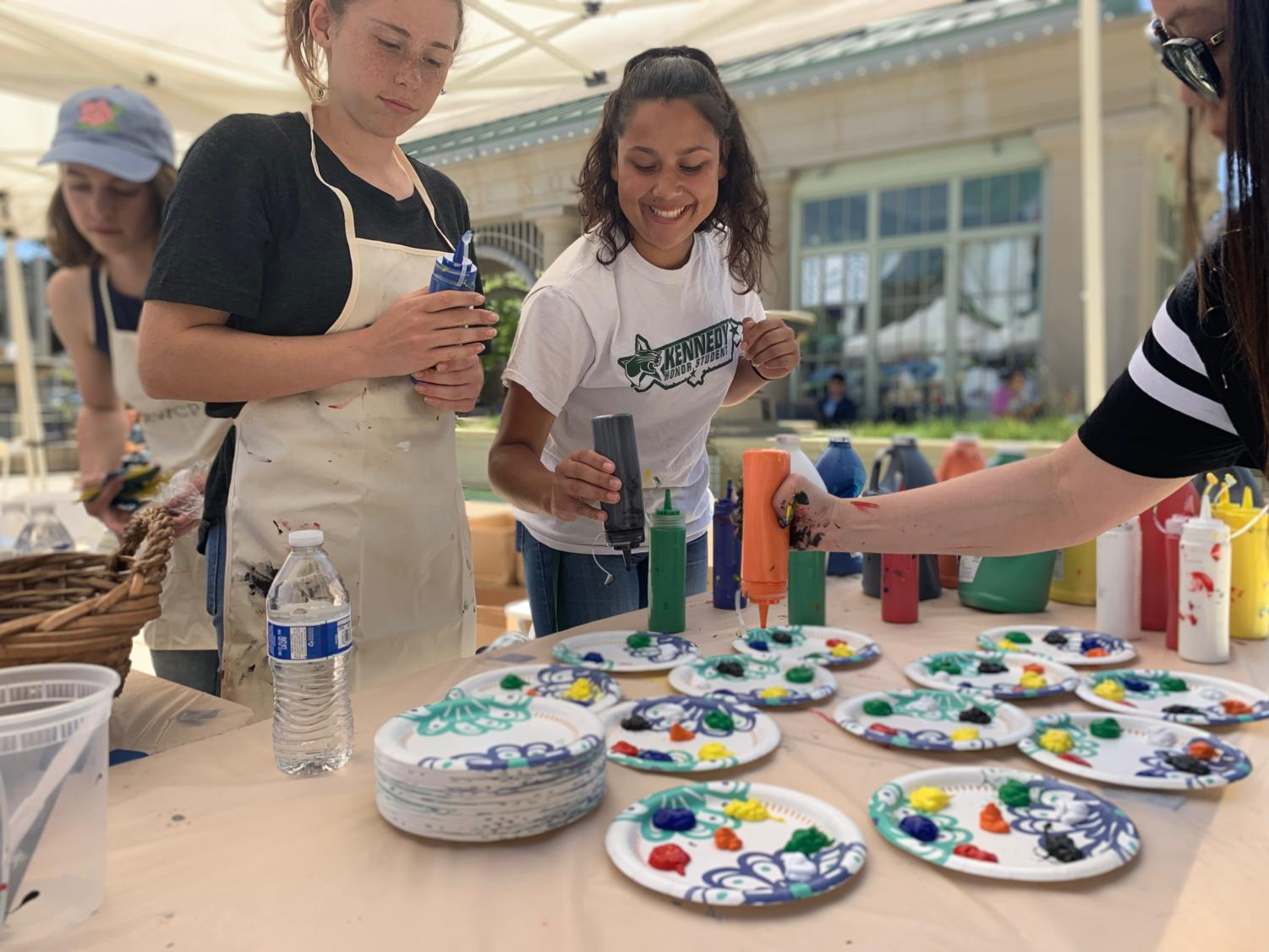 CAPA volunteers graciously squirt different colored paint onto paper plates.