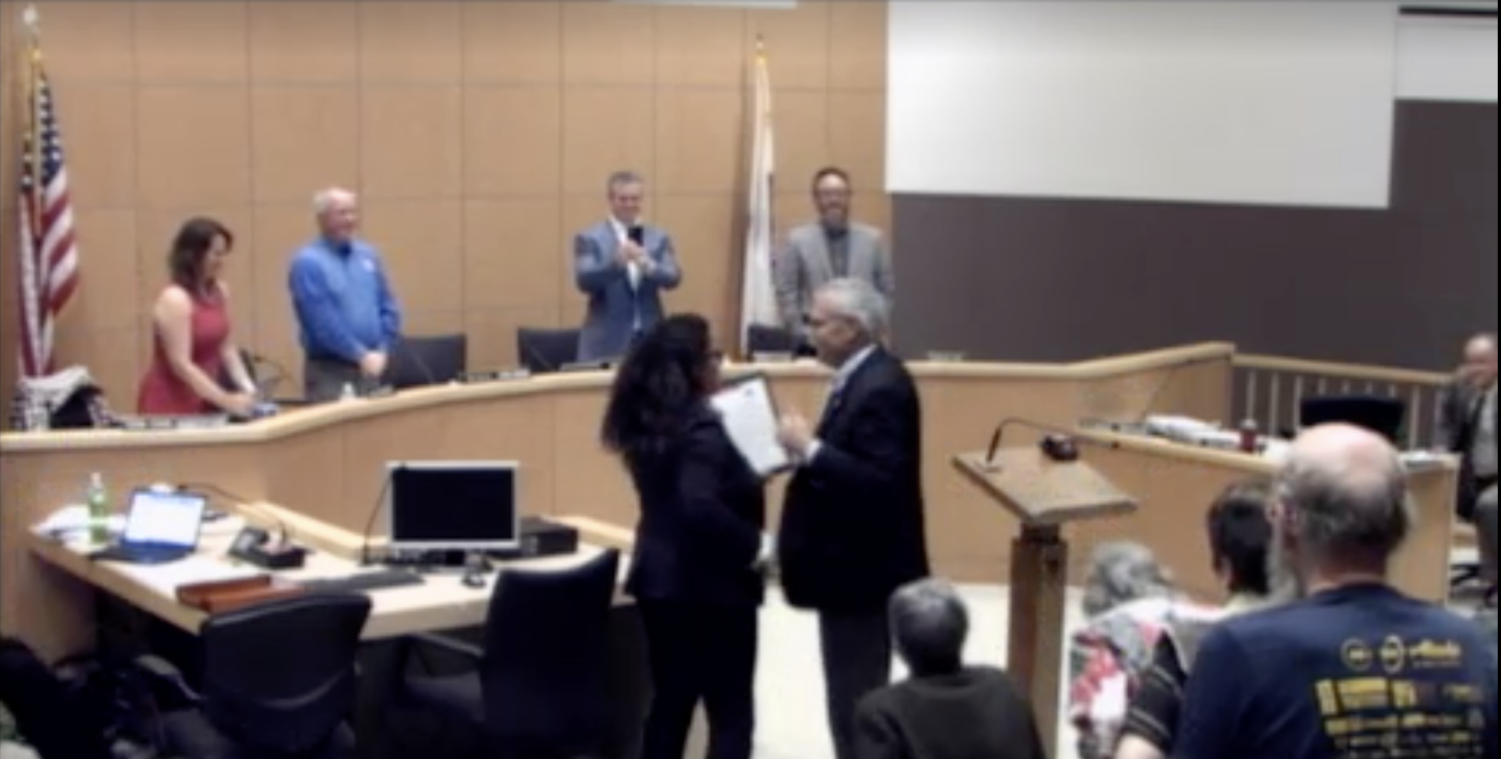 Mayor Davina Hurt gives outgoing city manager Greg Scoles a proclamation honoring his years of service.
