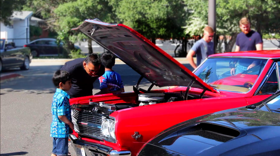 A+father+examines+the+engine+of+a+car+with+his+two+children.