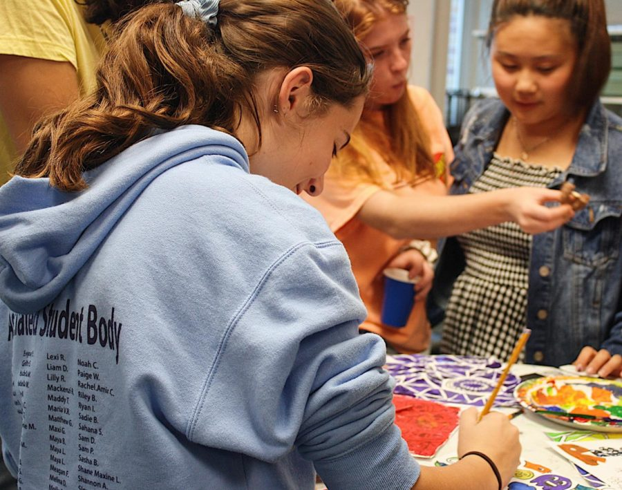 Isabella Peterson, a sophomore, paints a picture of a monster at the Reach Out Hangout.