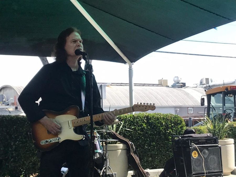 Stan Erhart plays his electric guitar alongside his band for attendees of the farmers' market.
