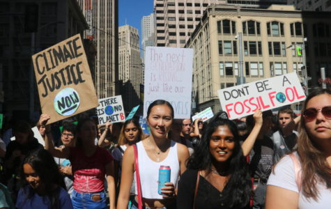 Teenagers wield signs demanding climate justice as they march through the streets of San Francisco on Sept. 20, 2019.