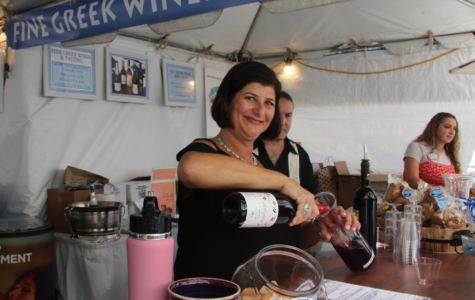 On opening day, one of the women working at the wine tasting booth pours a customer a bottle of wine.