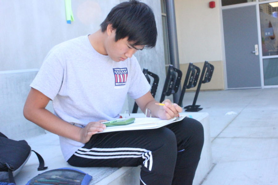 Jackson Young, a senior, works on his physics homework during lunch.