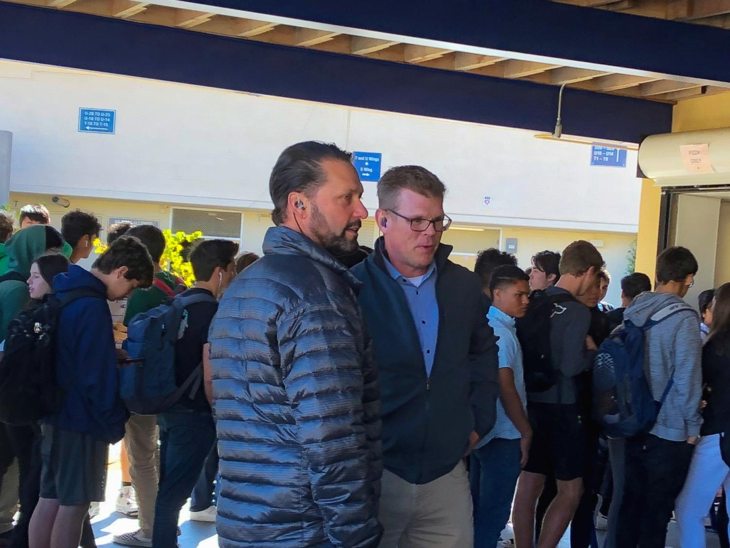 Grant Steunenberg and Gregg Patner talk to each other as they supervise students waiting in line for their lunch.