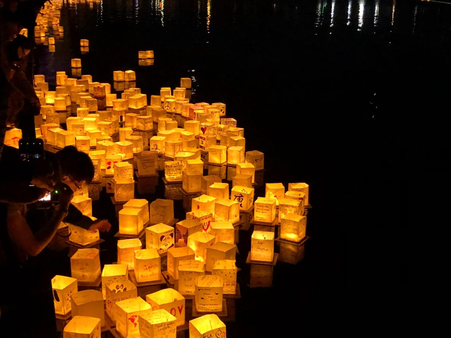 Lanterns are placed in the water as they begin to light up the festival