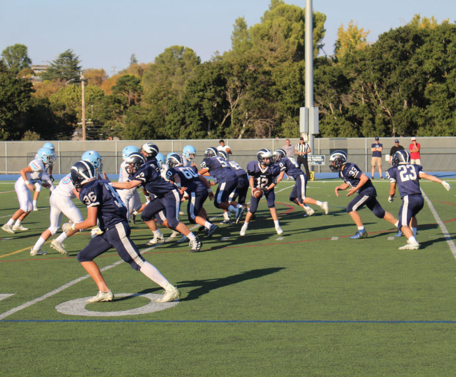 Jack+Wiessinger%2C+a+freshman+quarterback%2C+hands+the+ball+off+to+Nessel.